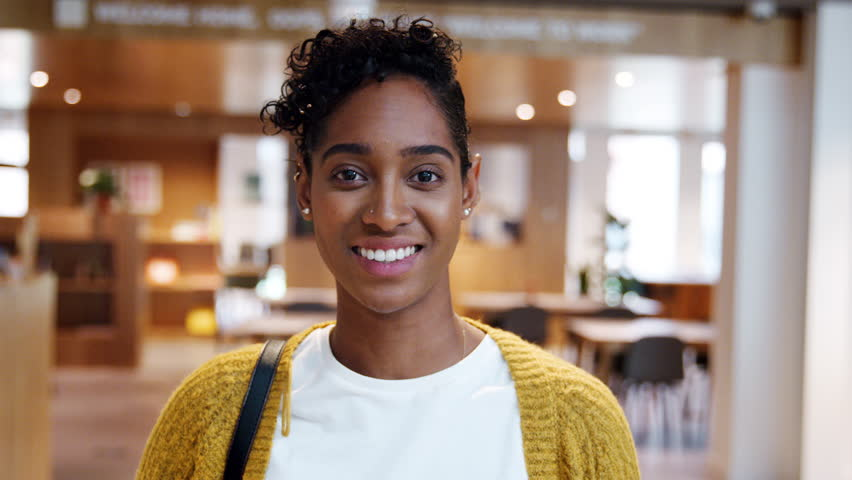 Young mixed race woman standing in a business lobby on her way out from work, looking to camera | Shutterstock HD Video #1021972975