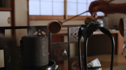 Cup of hot, steaming water being poured by tea master into a bowl in a traditional Japanese home with soft day lighting. Close up shot on 4k RED camera.