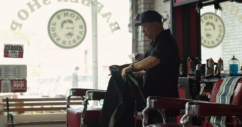 Skilled barber setting up shop before opening in interior hipster barbershop with soft day lighting. Medium shot on 4k RED camera on a gimbal.