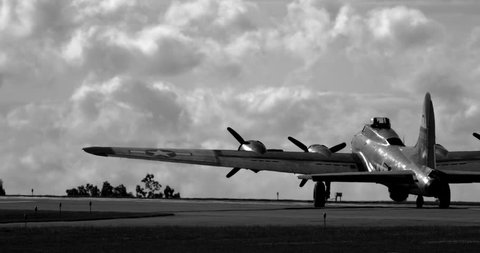 WWII B17 Flying Fortress airplane driving on tarmac towards runway - silhouetted in back and white