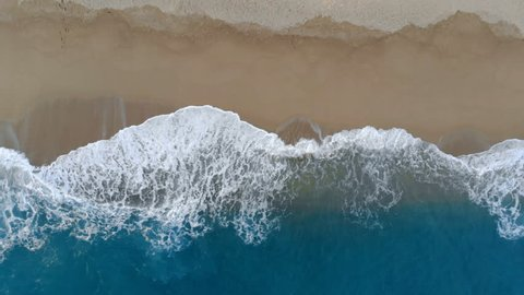 View from above of foamy waves and sandy coast