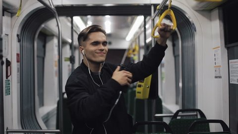 Portrait of handsome men in headphones listening to music and funny dancing in public transport. He holds the handrail