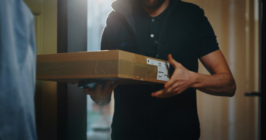 Happy young woman receiving and signing a parcel from mailman  delivered in her home. Shot with RED camera i 8K. Concept of courier, delivery, e-commerce, online shopping