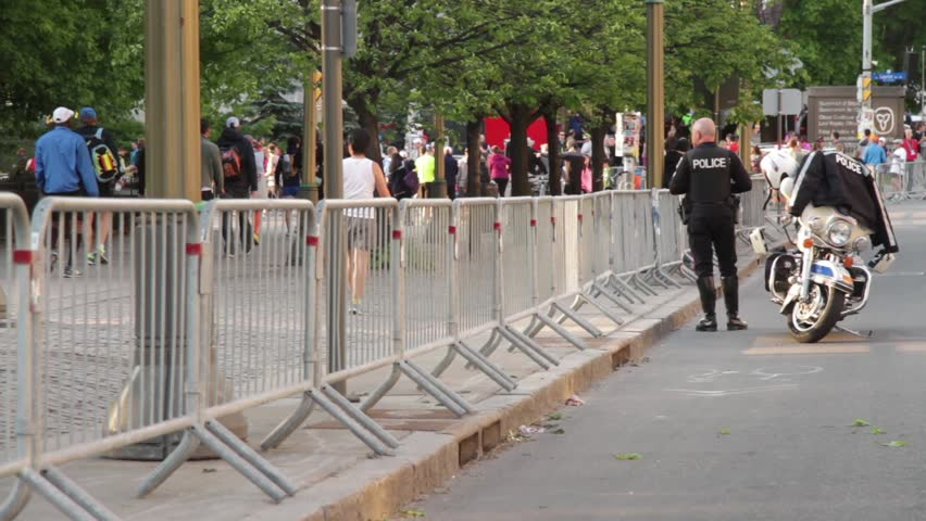 Ottawa, Canada - May 2015 - A police officer stands watch outside the gates of the Ottawa Marathon on guard for any sign of aggression in the wake of the Boston Bombings