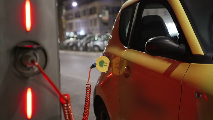 Electric car at charging station in the city street. Eco energy, transport and power supply. Environmentally conscious transportation vehicle plugged in charger terminal. 4K. | Shutterstock HD Video #1022098315