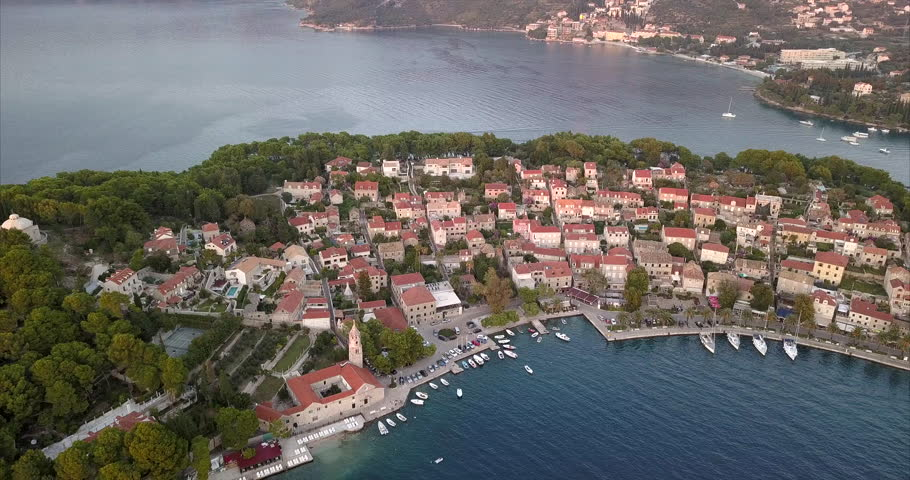 Small Croatian village built on the sea front, during sunset, filmed from the air