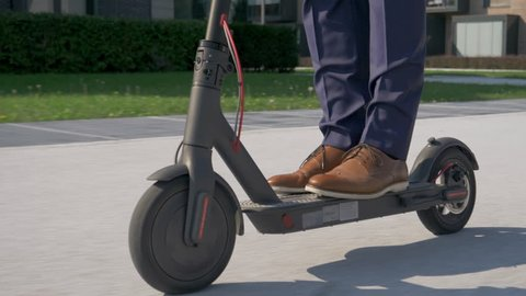 Close up - Adult male in business attire riding with electric scooter to work