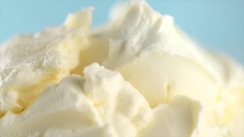 Mascarpone cream cheese close-up. Rotated mascarpone Italian soft milk cream closeup, on blue background. Homemade ice cream, yoghurt texture. 4K UHD video