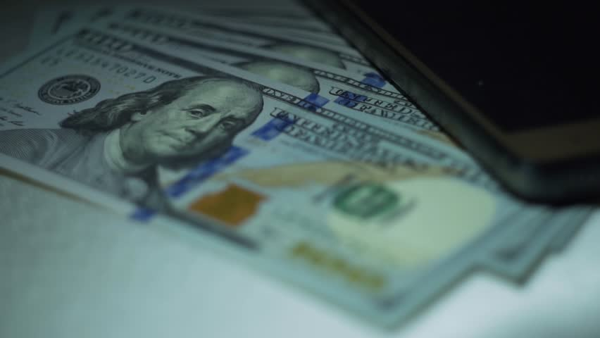 Dollars and smartphone. Close-up. | Shutterstock HD Video #1022147875