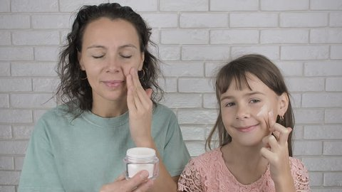 Mother and daughter moisturazing skin. Night routine. Using face cream.