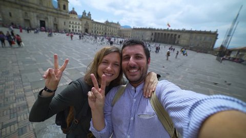 Happy young couple travelling in Colombia taking a selfie photo in the capital Bogota, smiling in the main square Bolivar in Calendaria district