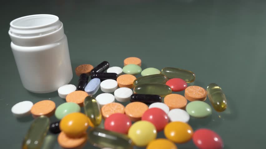 Prescription drugs are spilling from a bottle of pills. | Shutterstock HD Video #1022198245