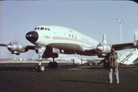 CIRCA 1956 - Passengers enjoy good food and a baby gets a bottle on a TWA flight.