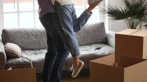 Happy couple first time buyers home owners embracing celebrating moving day, husband holding lifting wife among boxes after relocation into new flat, family goals, mortgage concept, close up view
