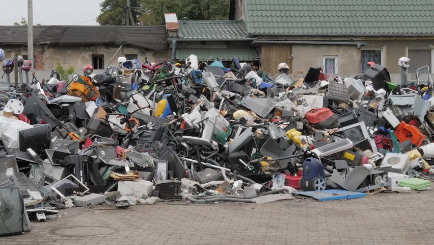 Unsorted plastic waste and old household appliances. Recycling center