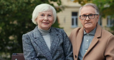 Portrait of the Caucasian senior couple sitting on the bench in autumn and smiling to the camera. Outdoor.