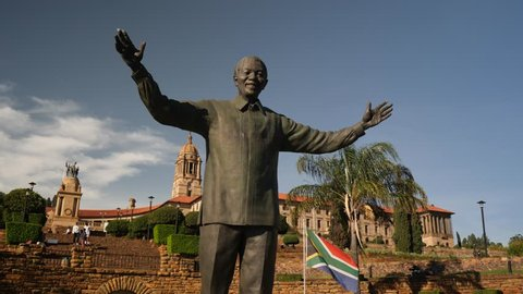 Pretoria, South Africa - circa January 2019: Nelson Mandela statue at the  sandstone Union Buildings, government offices, with South African flag flying in background on sunny day, dolly move forward