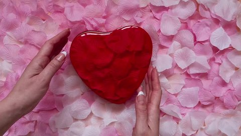 Top view: woman opens a red heart-shaped gift box. The lid of the box is decorated with red rose petals. Rose petals are also inside the box. Red heart valentines day concept