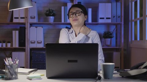 slow motion woman at work suffering from neck pain. elegant asian office lady tired and stressed after working for long time at night in company. hard overwork female worker using laptop computer.