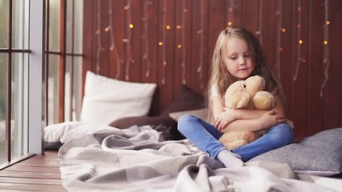 Adorable little girl with long blond hair and freckles sitting cross-legged on the bed gently hugging her plush dog, looking down and up at the camera. Slow motion