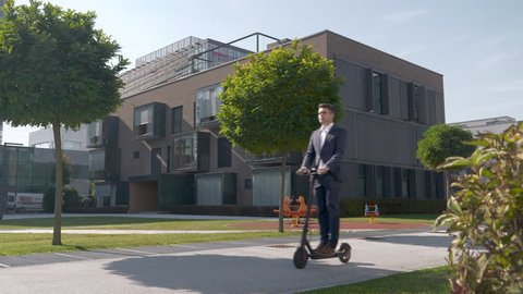 Slow motion - Man in a suit riding electric scooter