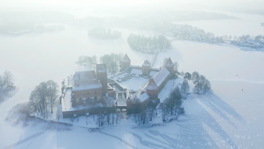 Winter lake island castle of Trakai, Lithuania, aerial view. Trakai was one of the main centers of the Grand Duchy of Lithuania and the castle held great strategic importance. | Shutterstock HD Video #1022372515