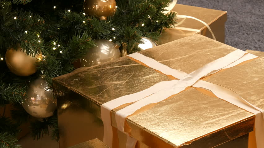 Large gift boxes, present of gold color under the Christmas tree in the mall. Christmas and New Year's gift decor. Gift gold box with gold satin ribbon | Shutterstock HD Video #1022388265
