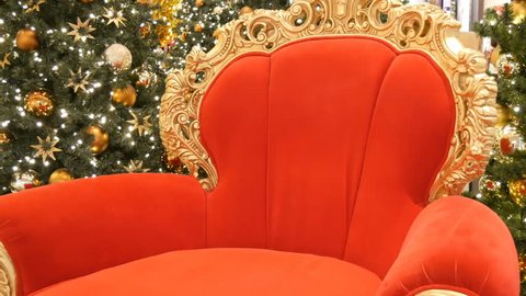Red chair of Santa Claus or St. Nicholas near christmas tree at the mall. Christmas decor shopping center.