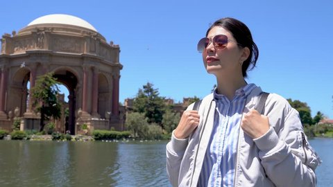 elegant girl travel backpacker in sunglasses sightseeing in palace of fine arts under sunshine in summer vacation trip. asian woman looking to blue sky smiling with birds resting flying floating pond