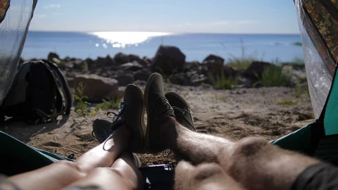 Close-up view of young couple's legs lying in camping tent with feet joined while resting after hiking day. Happy lovers enjoying beautiful sea view and relaxing in the evening.