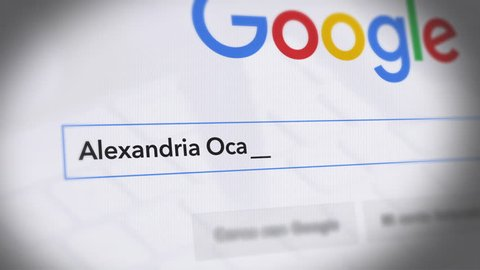 USA-Popular searches in 2019 Google Search Engine - Search For Alexandria Ocasio-Cortez Monitor with reflection hands typing a search on google