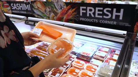 Female Customer Buying Salmon Fish And Red Caviar In Supermarket.