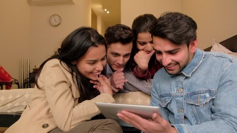 Indian friends focused and transfixed to a portable handheld electronic device tablet as they share entertaining stuff, handheld gimbal stabilized shot