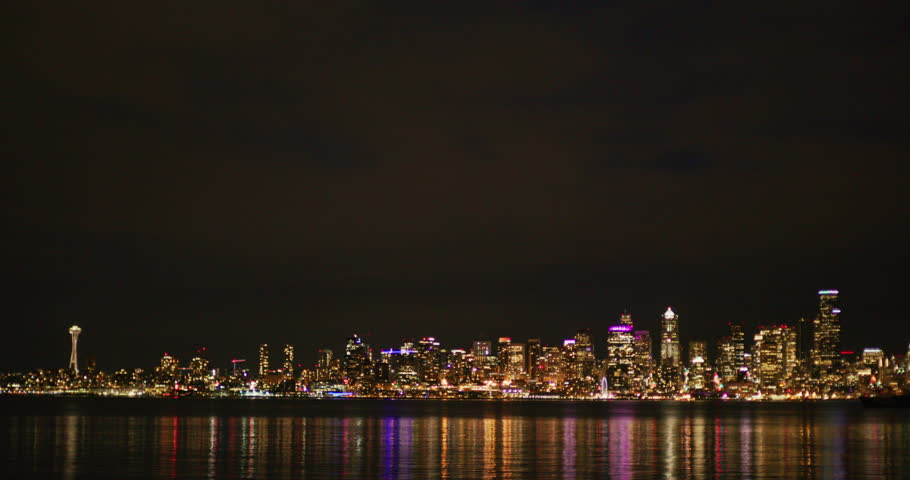 Night Tilt down from night sky view Seattle skyline across Puget Sound