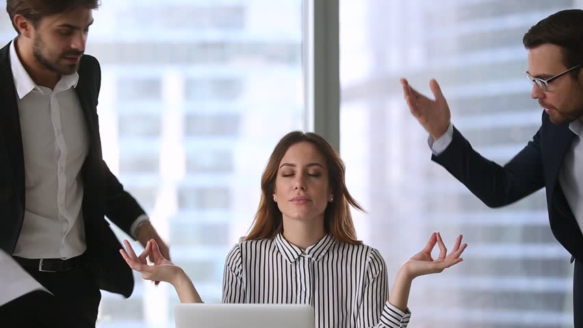 Calm businesswoman professional taking break meditating at work ignoring angry colleagues disturbing clients, mindful healthy female boss doing yoga feeling no stress zen balance at office workplace | Shutterstock HD Video #1022497315