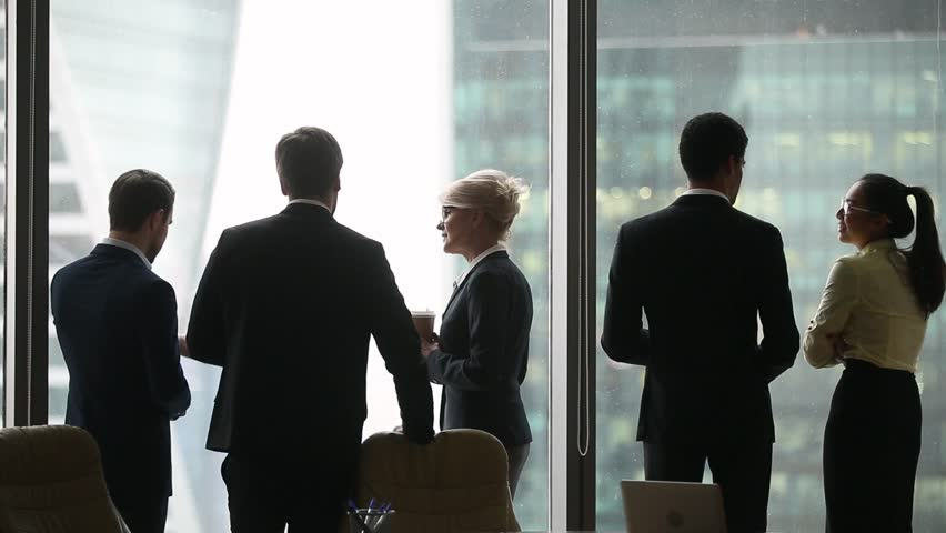 Rear back view of diverse colleagues group talking at work break, international business people silhouettes have corporate discussion near window, racial segregation discrimination in office concept