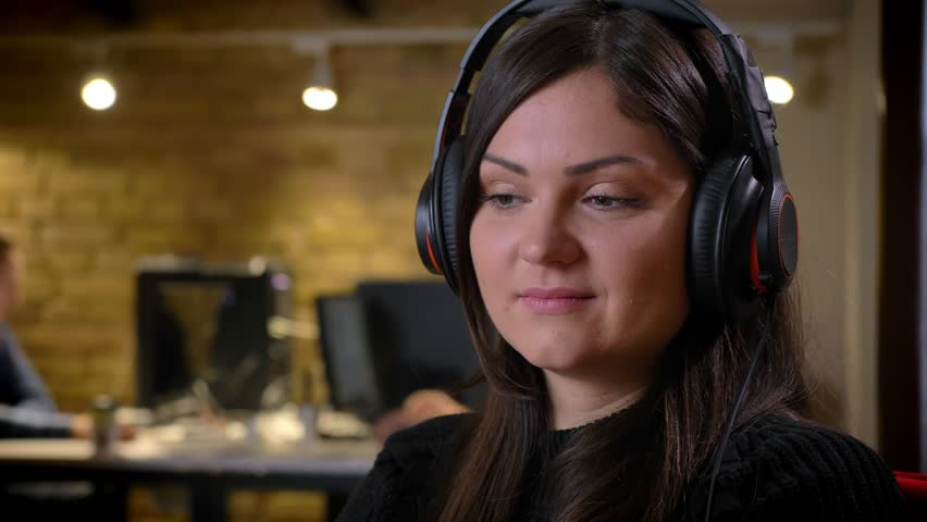 Closeup portrait of adult caucasian businesswoman in headphones turning and looking at camera smiling being on the workplace #1022551915
