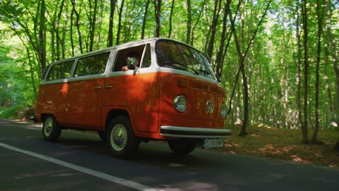 Driving an orange bus on a forest road.
