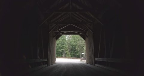 Pushing slowly forward towards the road through the dark, dramatic tunnel of the public Lowe's covered bridge in Maine with a logging truck passing quickly by.