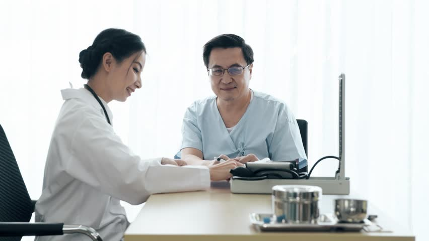 Doctor with patient. Young female medical doctor talking to a senior patient at hospital. Taking notes. Senior care medical and insurance concept. | Shutterstock HD Video #1022583415