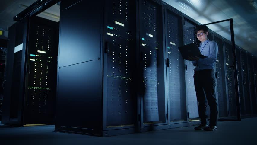 In Data Center: Male IT Technician Running Maintenance Programme on a Laptop, Controls Operational Server Rack Optimal Functioning. Modern High-Tech Telecommunications Operational Super Computer.   Shutterstock HD Video #1022590645