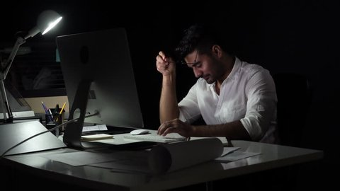 Fatigued sleepy workaholic Asian man yawning while working late at night in dark office
