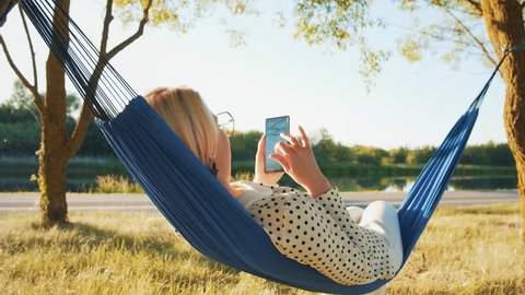 Happy girl resting on a hammock using a smart phone on vacation