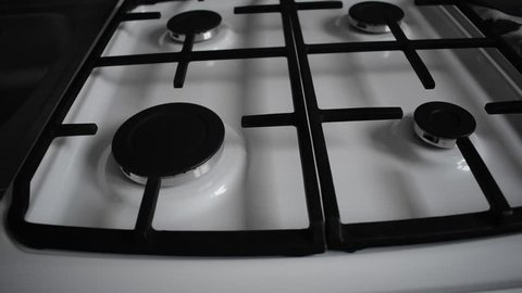 Natural gas inflammation in stove burner. Kitchen burner turning on. Turns on gas stove burners. Stove top burner igniting into a blue cooking flame. Blue gas.