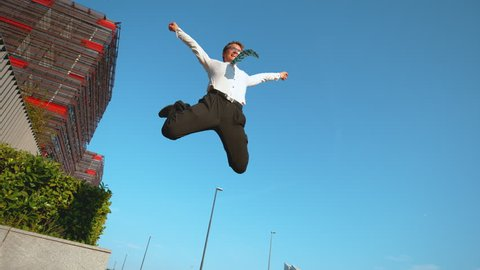 TIME WARP LOW ANGLE: Happy Caucasian businessman celebrates finishing work before going on his summer vacation. Carefree young man jumping high in the air while celebrating his first job promotion.