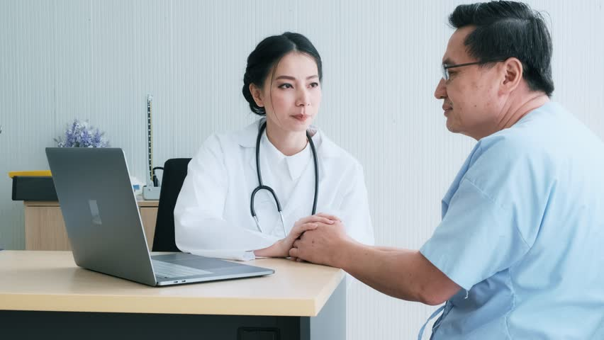 Doctor with patient. Young female medical doctor talking to a senior patient at hospital. Looking at her laptop to discuss medical examination result. Senior care medical and insurance concept. | Shutterstock HD Video #1022636845