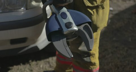 Metal cutter held by firefighter as he prepares to train for responding to car accidents and rescuing trapped people.