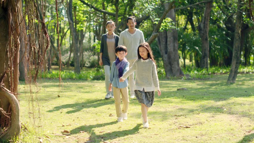 Asian family with two children relaxing walking in park