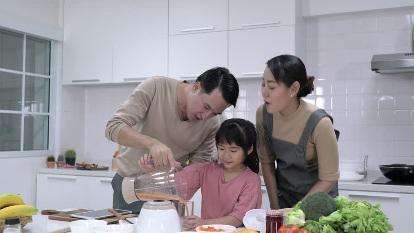Asian family make smoothie together in kitchen at home. Little girl with father and mother make drink refreshment. Concept of happy family and activity holiday. | Shutterstock HD Video #1022688685
