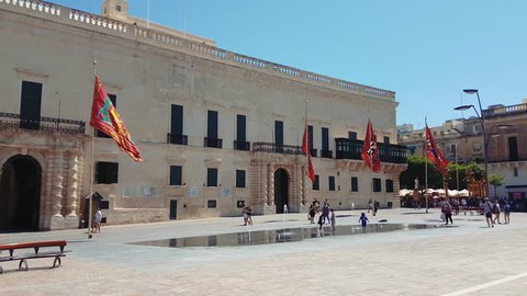 Valletta, Malta - August 02 2016: Grandmasters Palace facade in St Georges Square. Day view of the Governors Palace with traditional Maltese architecture and tourists at the square on Republic Street.